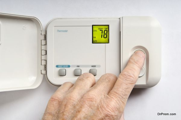 Setting wall thermostat to 78 degrees Fahrenheit as a conservation measure in summer. Digital thermostat display is backlit.