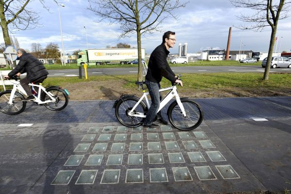 """Cyclists use the SolaRoad, the first road in the world made of solar panels, during the official opening in Krommenie on November 12, 2014. The Netherlands unveiled the world's first solar bike path, a revolutionary project to harvest the sun's energy that could eventually also be used on roads. The so-called """"SolaRoad"""" bike path is made of concrete modules each measuring 2.5 by 3.5 metres (eight by 11 feet), embedded with solar panels covered in tempered glass.  AFP PHOTO/ANP/EVERT ELZINGA == NETHERLANDS OUT ==        (Photo credit should read EVERT ELZINGA/AFP/Getty Images)"""