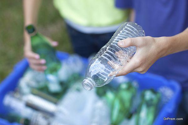 Hands placing bottles in recycling bin