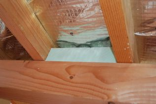 Filling in gaps in the eaves with reclaimed insulation foam