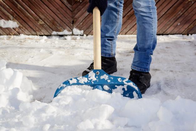 young-man-shoveling-snow-driveway-near-garage_123211-145