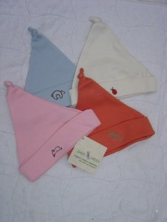 Product Image set of four newborn baby hats in pink, blue, unbleached and saffron
