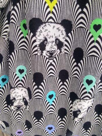 close up of b&w pandas on scallop feathered background with pops of rainbow colour