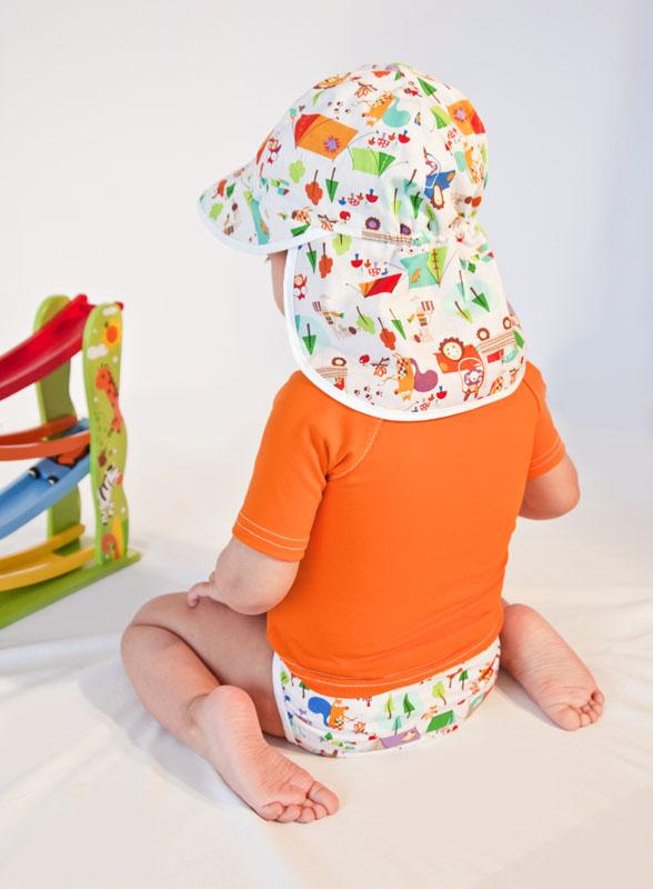 baby wearing bright sun shirt, cloth diaper and sun hat