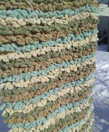 striped and tufted floor mat hanging on line on sunny winter day in Canada