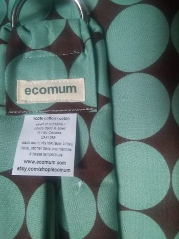 close up of slight dye flaw on fabric printed with large sage circles against chocolate coloured background