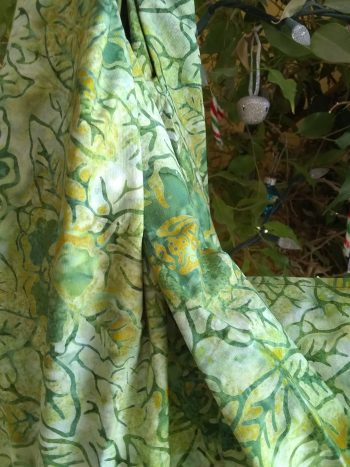 bright green batik midwifery weigh sling handing in front of tree