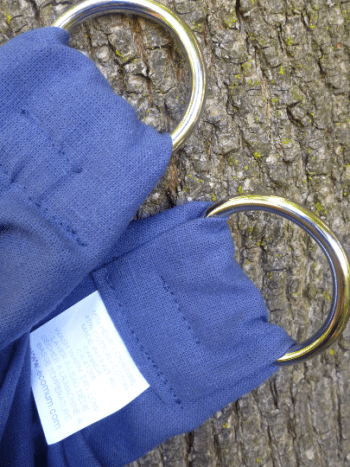 ring ends of blue midwifery weigh slings against tree bark