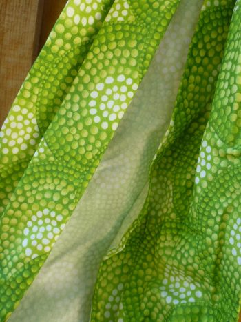 detail of midwifery weigh sling made from spring-like shades of green in a circular dot pattern.