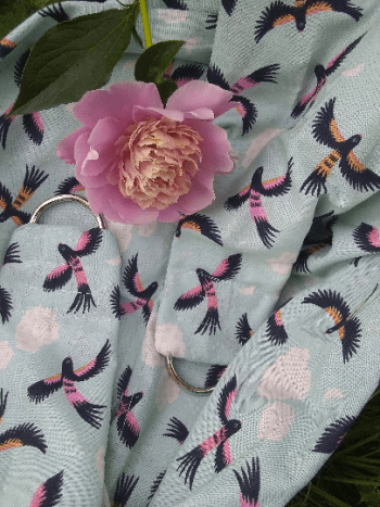 weigh sling of light blue background, all over pattern of clouds, and black and pink parrots in flight. Pink peony in foreground