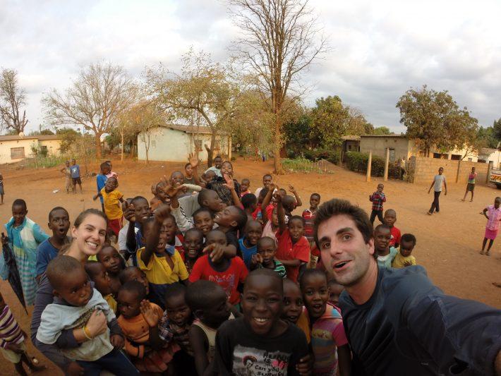Gabriele Garcia e Felipe Brescansini, fundadores da ONG Think Twice Brasil, com crianças no Zimbábue