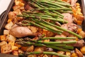 Pilons de poulet, courge, patates et asperges sur une plaque