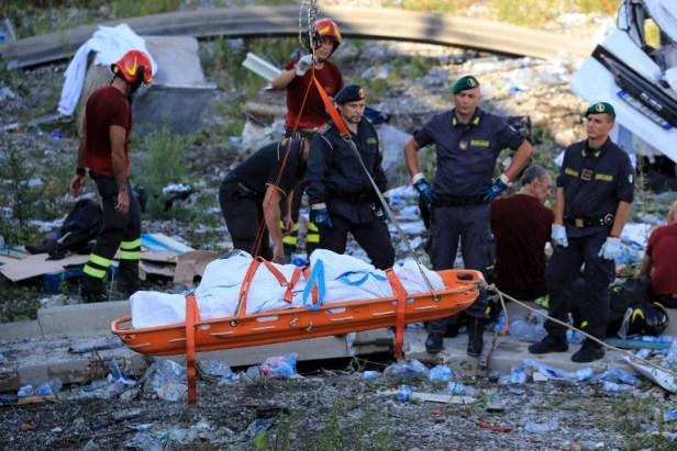 Les sauveteurs et les forces de sécurité observent comme un corps récupéré évacué sur le site où le pont de l'autoroute de Morandi s'est effondré à Gênes le 14 août 2018. Valery HACHE / AFP