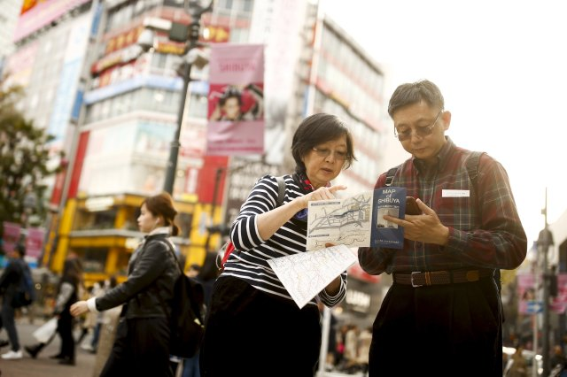 People look at a street map at the Shibuya junction, which is popular among tourists, in Tokyo