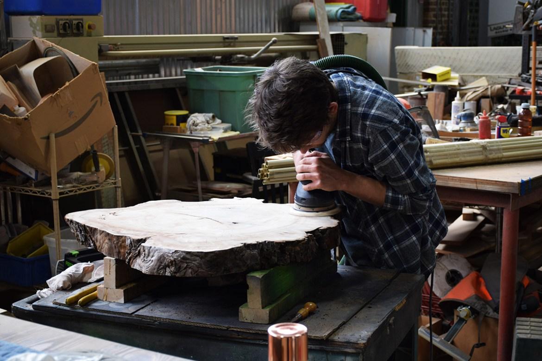 Our newest wood shop craftsman, Matt, sanding the slab!