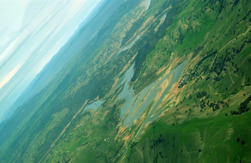 Aerial view of river surrounded by green landscape