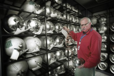 Man checking a gas bottle in room with shelves full of silver coloured gas bottles