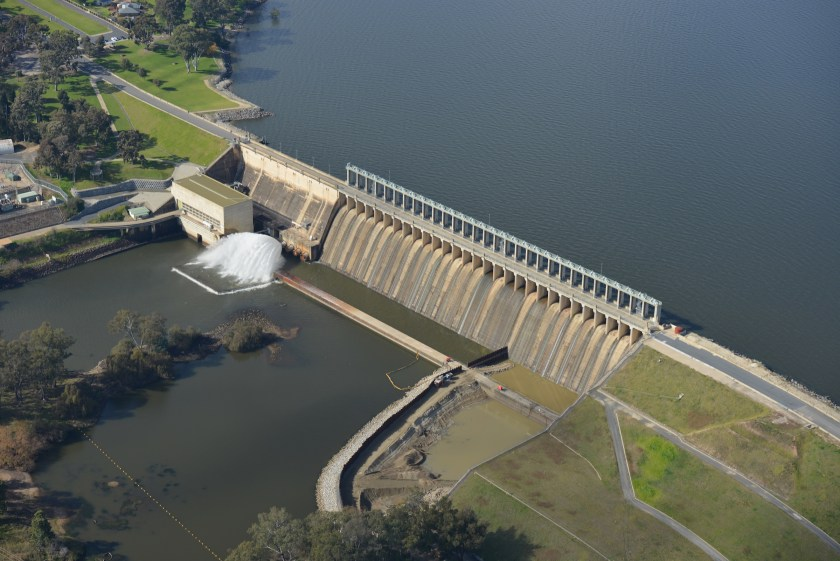 Aerial view of dam with lake on one side and spillway on the other
