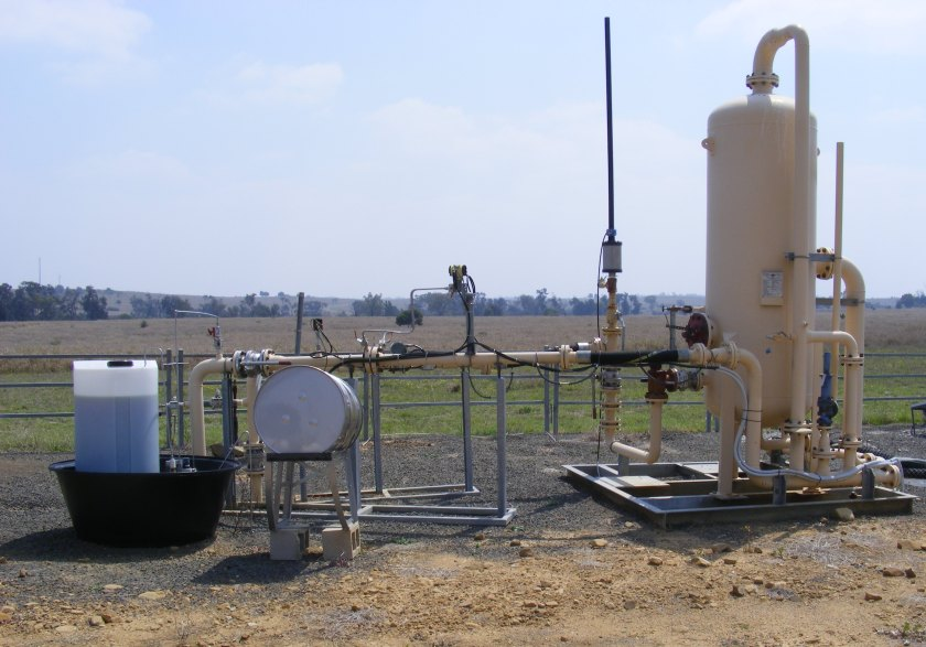 A large cylinder and with pipes coming from the ground in a paddock