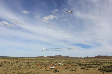 A helicopter with a large ring suspended from it hovering over landscape