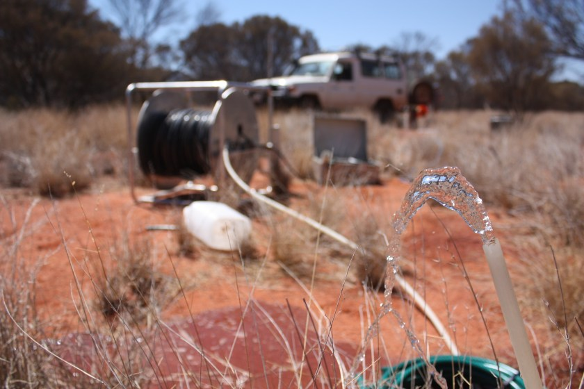 Water pouring out of a hose with outback setting in background