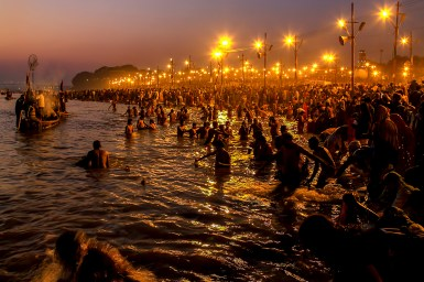 People entering a river at night with lights along banks