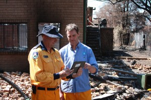 Two men looking at a tablet device with burnt houses in background