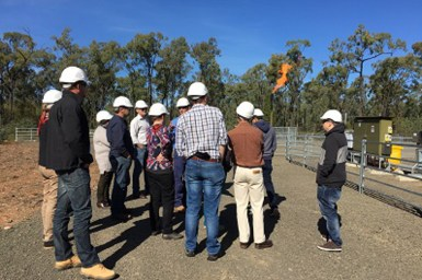 Group of people with hard hats on standing near a CSG well