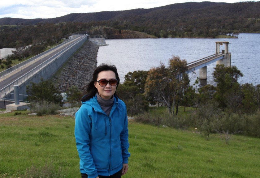 woman with dam wall in background
