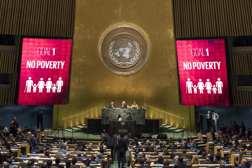UN general assembly with two big screens either side of the podium saying Goal 1 No Poverty