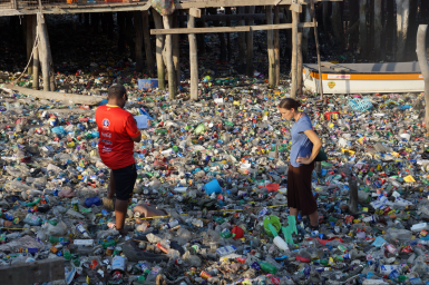 people standing in a sea of plastic in a waterway