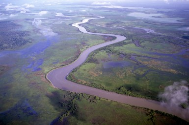 aerial of river winding through coastal flood plain