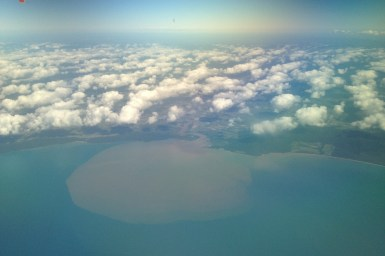 aerial view of coast with plume in water