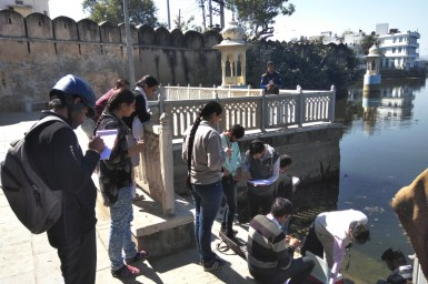 students taking notes and water samples on the steps leading into a river