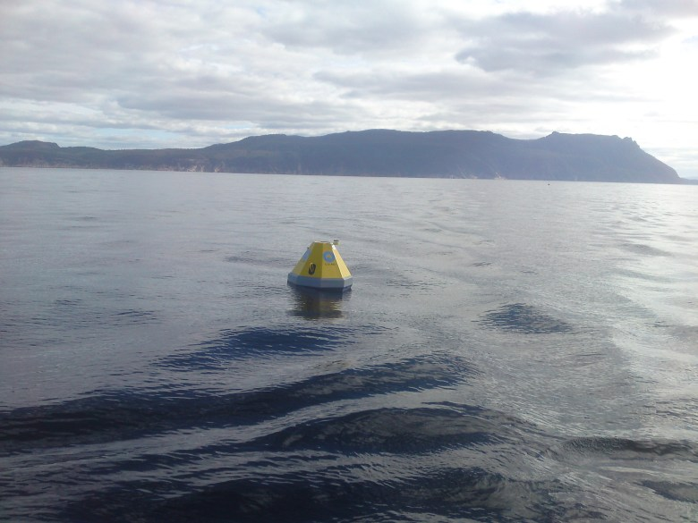 mooring buoy floating on ocean surface, island in the distance