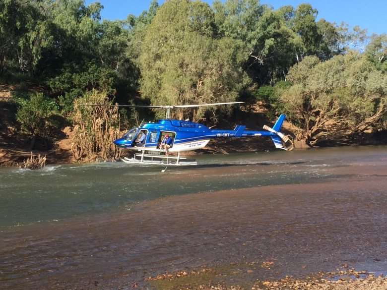 helocopter hovering over a river with a man in the helicopter holding a tube down to the water