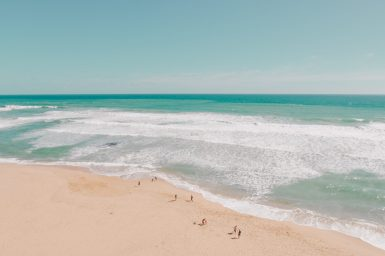 Super-wide view of a beach with ocean in the distance.