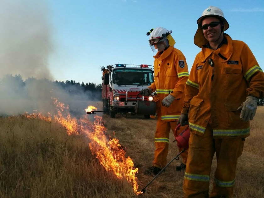 Two people in protective clothing by a fire