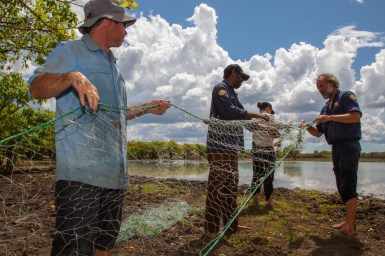 Four people holding and inspecting a green fishing net on the edge of water body.