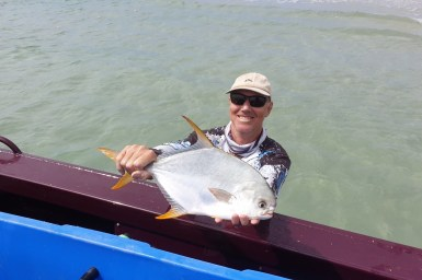 Fisherman with a pompano fish.