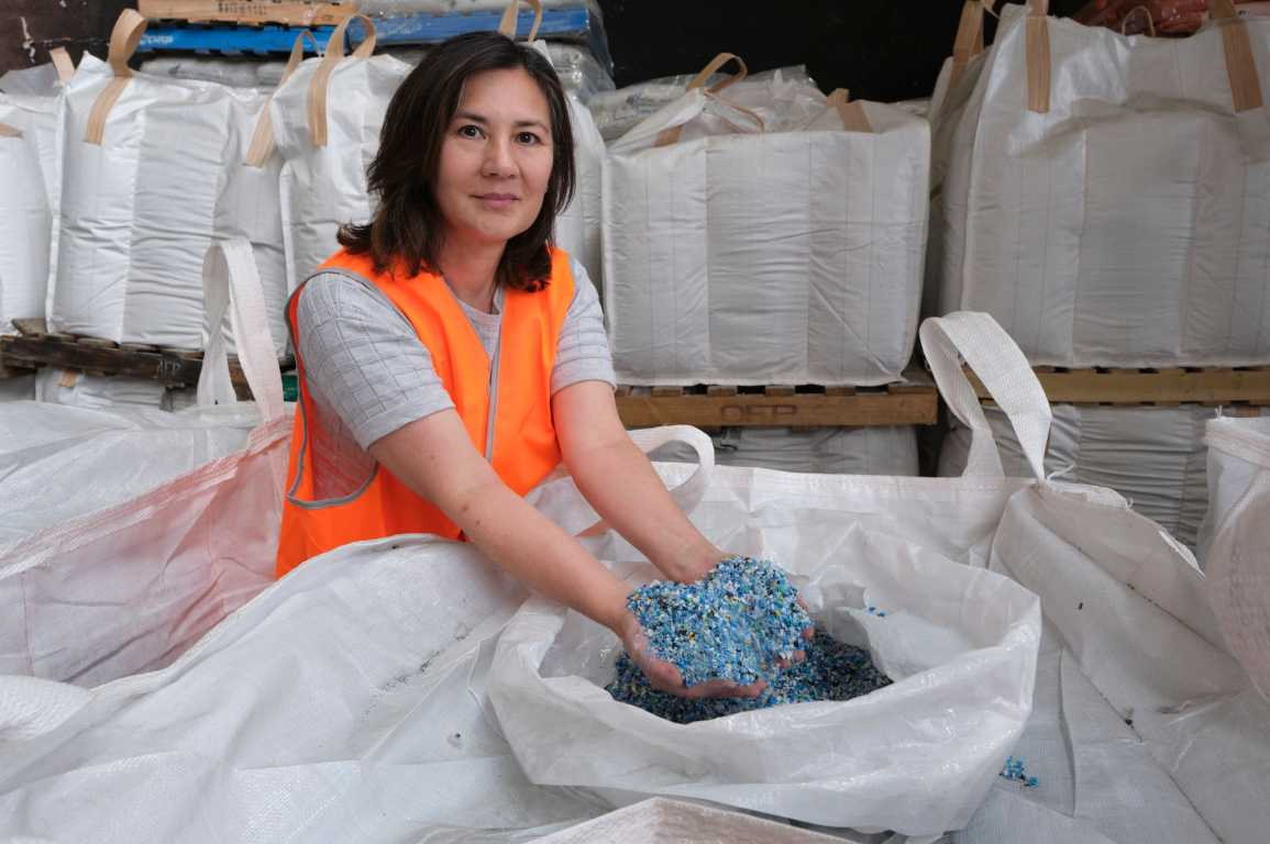 CSIRO's Deborah Lau looking at the camera with her hands in a bag of small fragments of plastic