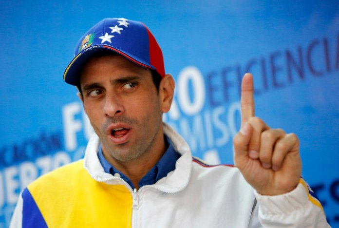 Miranda's state governor and opposition leader Henrique Capriles speaks during an interview with Reuters in Caracas February 26, 2014. One month ago, Capriles was Venezuela's undisputed opposition leader, espousing a vision of dialogue and measured dissent towards the socialist government. With a narrow but bruising presidential election defeat behind him and the next election not due until 2019, the state governor saw good government in opposition strongholds and grassroots work with the poor as the best way to build support. Now, though, an explosion of protests has put President Nicolas Maduro under pressure and also exposed rifts inside the opposition as a rival to Capriles takes a more prominent role. Picture taken February 26, 2014. REUTERS/Marco Bello (VENEZUELA - Tags: POLITICS HEADSHOT)
