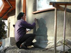 Angela drawing beautiful creatures on our cob home during one of her visits