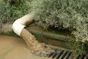 polluted runoff pouring from a pipe directly into a storm drain