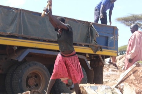 Alice Loumo using all her energy to break stones at the mining site in Kosoroi Tapac subcounty