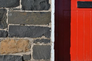 red shop door and stone wall eyemouth