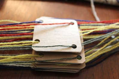 3. Tie the bunch of yarns on one side. Stack the cards on top of one another as you thread them without disturbing the order