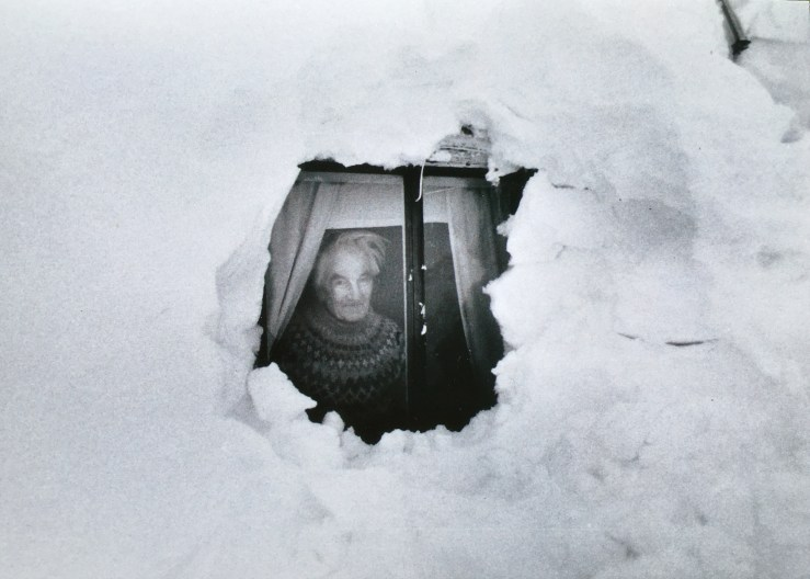 Image of an old man looking out a very snowbound window