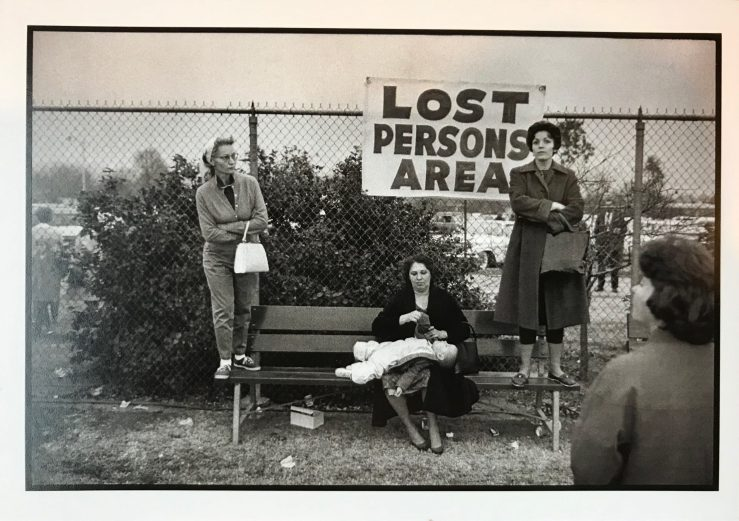 "image of several people in front of a sign reading ""lost persons area"""
