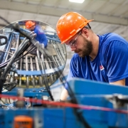 Worker working on a machine that could be connected with IIoT Devices to gather data and make improvements.